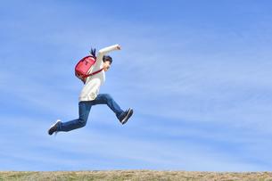 青空でジャンプする小学生の女の子(ランドセル、芝生広場)の写真素材 [FYI02919744]