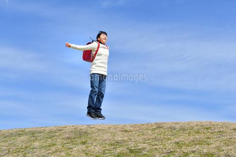 青空でジャンプする小学生の女の子の写真素材 [FYI02919844]