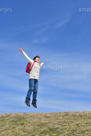 青空でジャンプする小学生の女の子の写真素材 [FYI02919846]