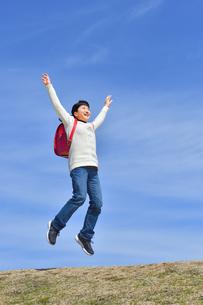 青空でジャンプする小学生の女の子の写真素材 [FYI02919848]