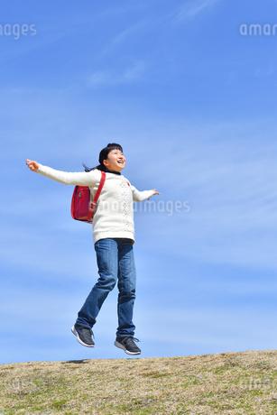 青空でジャンプする小学生の女の子の写真素材 [FYI02919849]