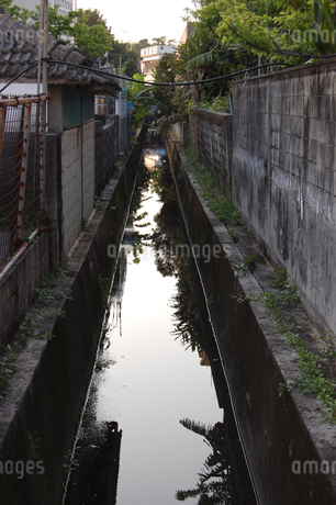 田舎町の小さな川に風景が反射しているの写真素材 [FYI02922403]