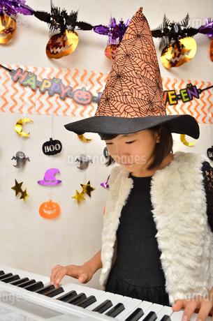 ハロウィンパーティーでピアノを弾く女の子の写真素材 [FYI02922568]