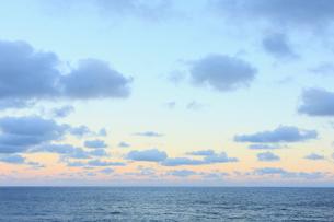 夕暮れの海茜色に染まる空と雲と水平線の写真素材 [FYI02923521]