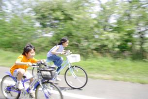 自転車でサイクリングロードを走る姉弟の写真素材 [FYI02927541]