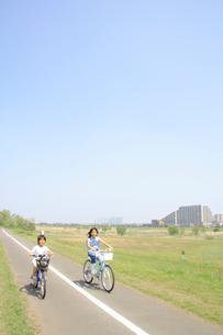 自転車でサイクリングロードを走る姉弟の写真素材 [FYI02927542]
