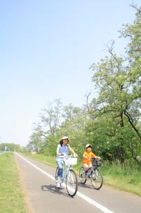 自転車でサイクリングロードを走る姉弟の写真素材 [FYI02927545]