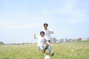 野原でサッカーを楽しむ親子の写真素材 [FYI02927550]