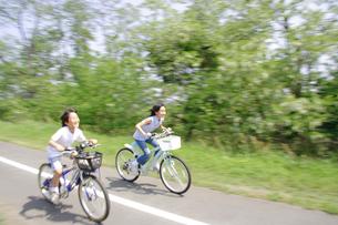自転車でサイクリングロードを走る姉弟の写真素材 [FYI02927552]