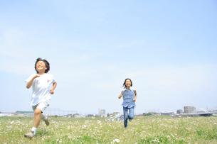 野原を走る姉弟の写真素材 [FYI02927557]
