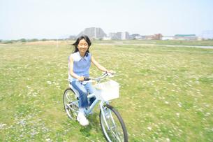 野原を自転車で走る女の子の写真素材 [FYI02927561]