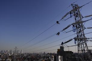 送電線で働く人たちと新宿副都心の街並みの写真素材 [FYI02927700]