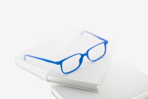 白い本に青いフレームのメガネの写真素材 [FYI02927780]
