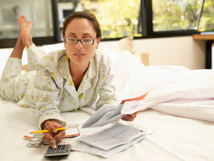 Young woman counting bills on bedの写真素材 [FYI02928590]