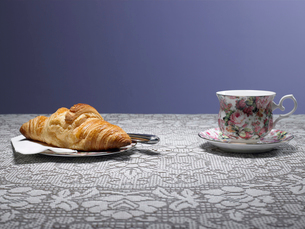 Tea cup and croissant on tableの写真素材 [FYI02928644]
