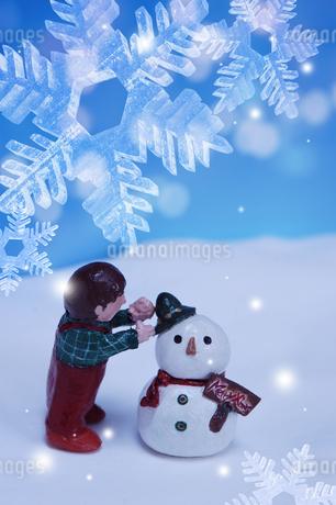 雪だるまに帽子をのせる男の子 クラフトの写真素材 [FYI02928659]