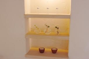 白壁の棚に置かれた小物の写真素材 [FYI02928675]