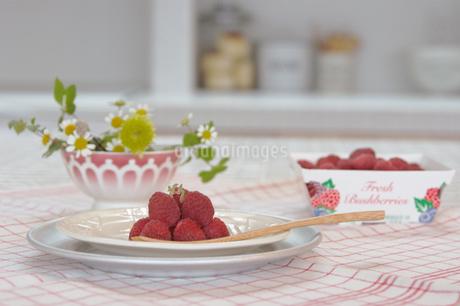 テーブルの上のラズベリーの盛られた皿の写真素材 [FYI02928679]