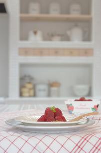 テーブルの上のラズベリーの盛られた皿の写真素材 [FYI02928681]