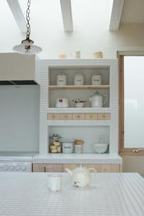 キッチンのテーブルに置かれたティーポットとカップと食器棚の写真素材 [FYI02928689]