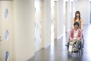骨折した彼氏の乗る車椅子を押す彼女の写真素材 [FYI02929915]