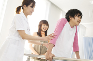 歩くリハビリをする彼氏と彼女と看護師の写真素材 [FYI02929934]