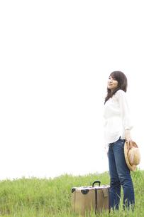 草原に立つ女性とトランクの写真素材 [FYI02930242]