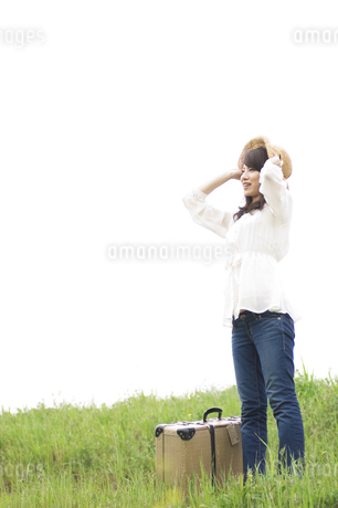 草原に立つ女性とトランクの写真素材 [FYI02930251]