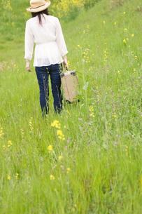トランクを持って草原を歩く女性の後姿の写真素材 [FYI02930266]