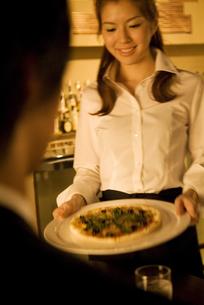 ピザを運ぶウエイトレスの写真素材 [FYI02930404]