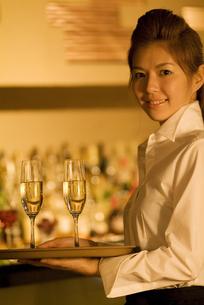 シャンパンを運ぶウエイトレスの写真素材 [FYI02930407]