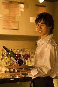 ワインとワイングラスを運ぶウエイターの写真素材 [FYI02930417]