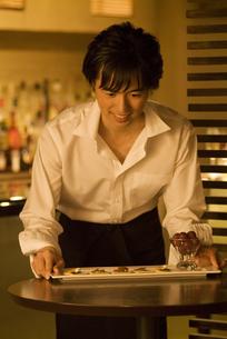 テーブルに料理の乗った皿を置くウエイターの写真素材 [FYI02930434]