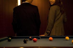 ビリヤード台に腰掛けるビジネスマンとビジネスウーマンの写真素材 [FYI02930455]