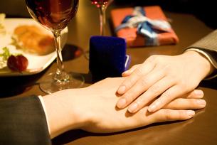 男性の手に手を添える女性の手元の写真素材 [FYI02930482]