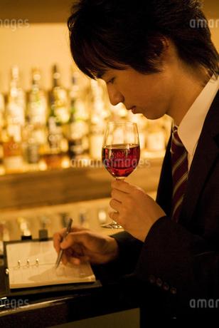 ワイングラスを持って手帳に書き込むビジネスマンの写真素材 [FYI02930520]