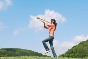 トランペットを吹きながら歩く女性の写真素材 [FYI02930639]