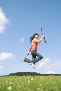 クラリネットを持ってジャンプする女性の写真素材 [FYI02930644]