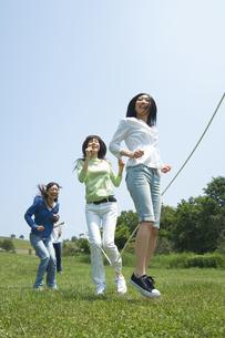 草原で縄跳びをしている3人の女性の写真素材 [FYI02930723]