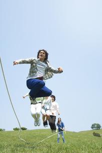 草原で縄跳びをしている若者グループの写真素材 [FYI02930730]