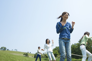 草原で縄跳びをしている3人の女性の写真素材 [FYI02930735]