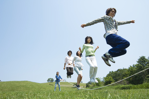 草原で縄跳びをしている若者グループの写真素材 [FYI02930736]