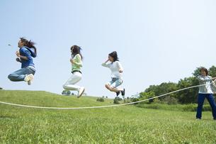 草原で縄跳びをしている3人の女性の写真素材 [FYI02930746]