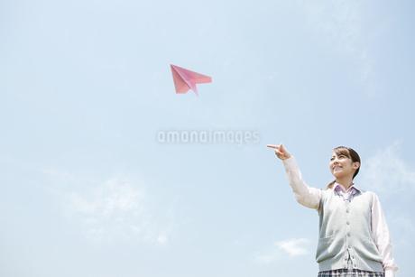 紙飛行機を投げる女子高生の写真素材 [FYI02930926]