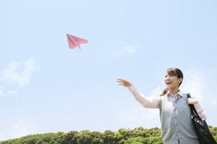紙飛行機を投げる女子高生の写真素材 [FYI02930938]