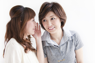耳打ちする女性2人の写真素材 [FYI02931023]