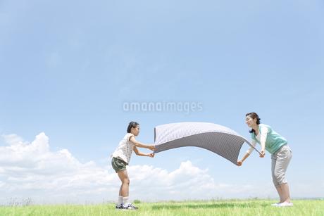 レジャーシートを広げる親子の写真素材 [FYI02931033]