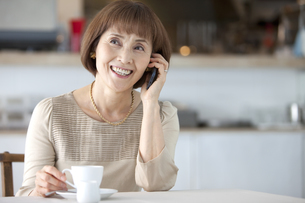 スマートフォンで通話している中高年女性の写真素材 [FYI02931238]