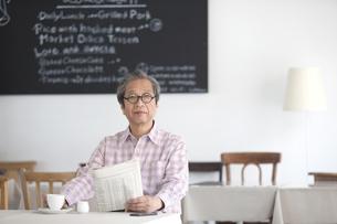 カフェで新聞を読む中高年男性の写真素材 [FYI02931248]