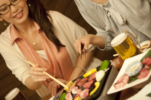 焼き肉を焼く女性の写真素材 [FYI02931292]